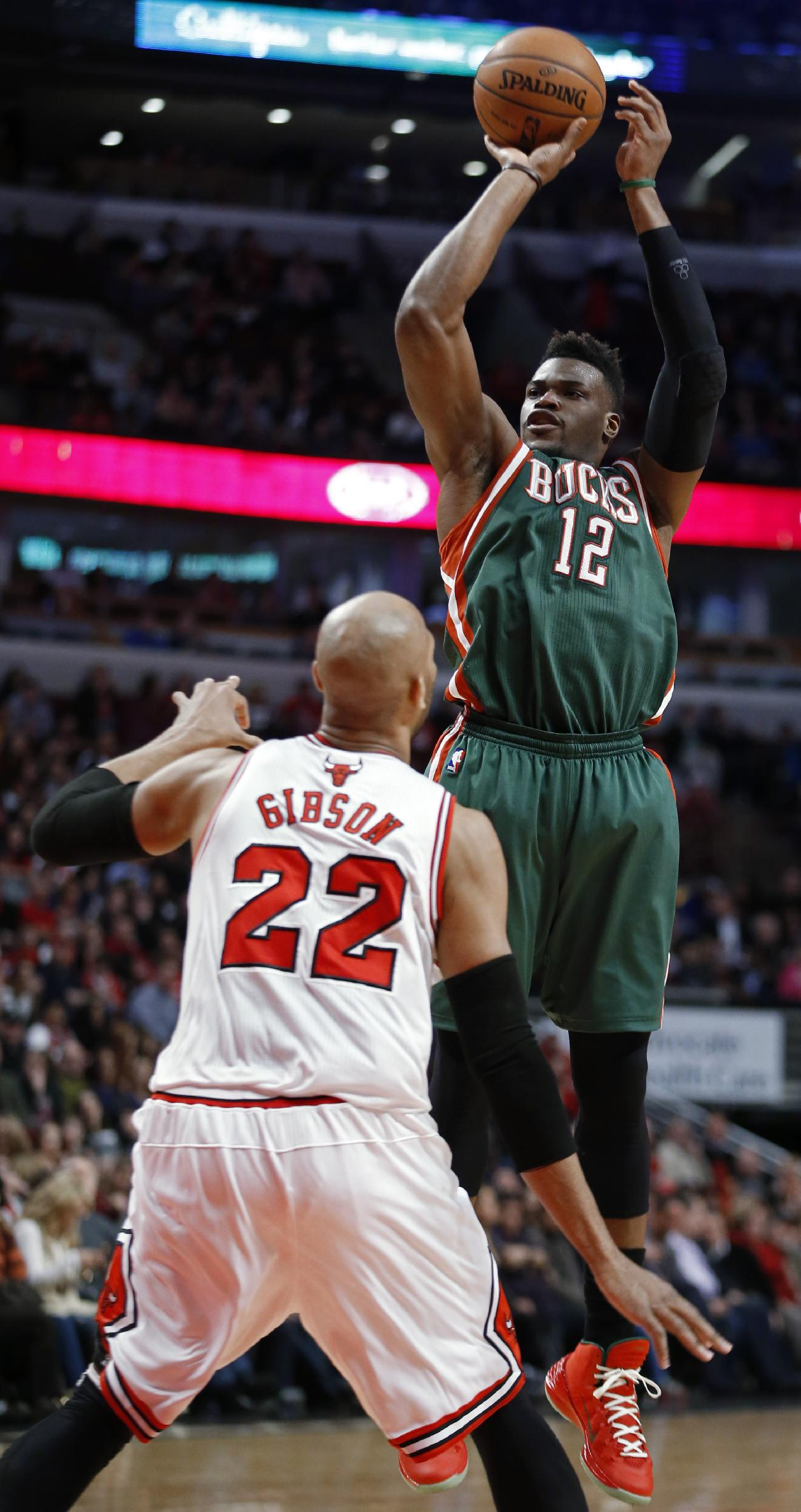 Milwaukee Bucks guard Jeff Adrien shoots over Chicago Bulls forward Taj Gibson during the second half of an NBA basketball game in Chicago, Friday, April 4, 2014. The Bulls won 102-90