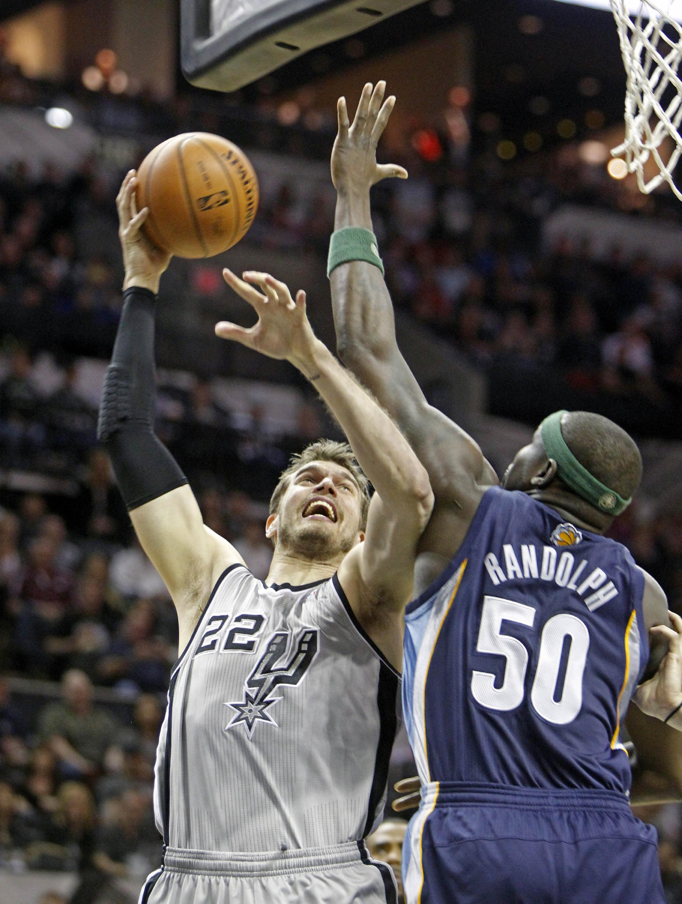 San Antonio Spurs' Tiago Splitter (22) goes up against the Memphis Grizzlies' Zach Randolph (50) during the first quarter of an NBA basketball game, Sunday, April 6, 2014, in San Antonio