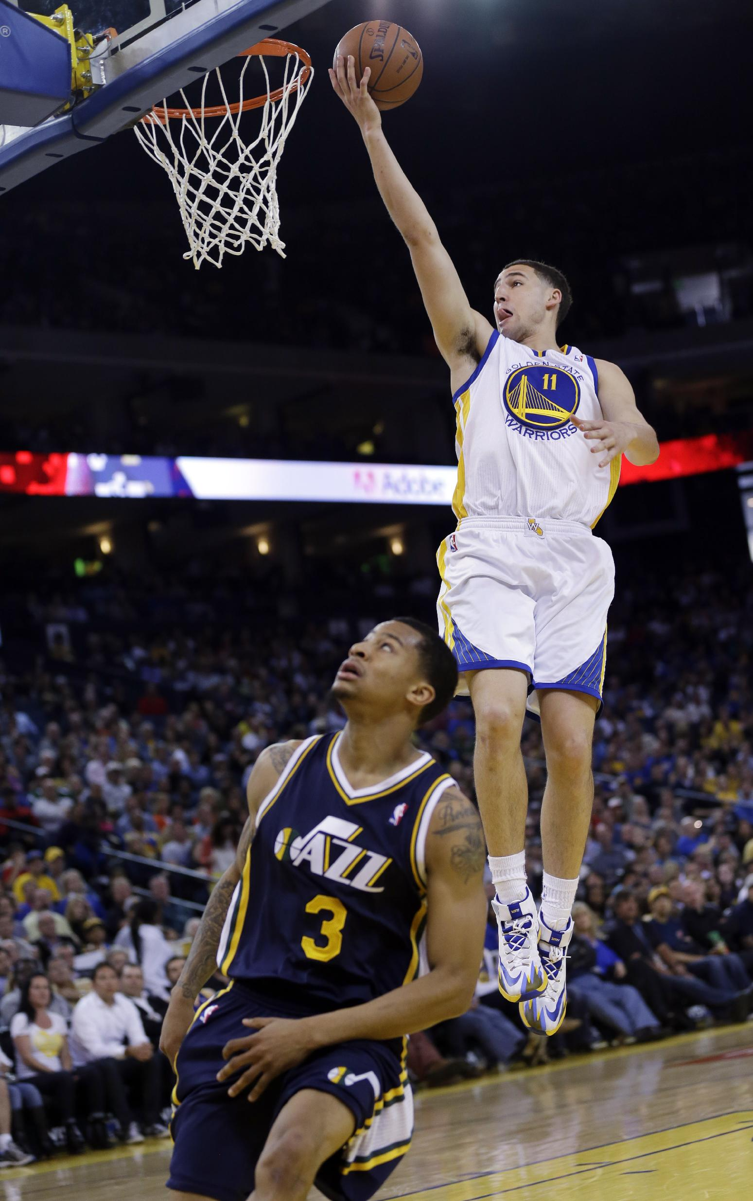 Golden State Warriors guard Klay Thompson (11) scores over Utah Jazz guard Trey Burke (3) during the first half of an NBA basketball game Sunday, April 6, 2014, in Oakland, Calif