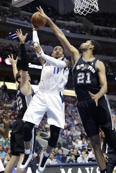 Dallas Mavericks guard Monta Ellis (11) drives between San Antonio Spurs forward Tim Duncan (21) and center Tiago Splitter (22), who stop his shot during the second half an NBA basketball game Thursday, April 10, 2014, in Dallas. The Spurs won 109-100