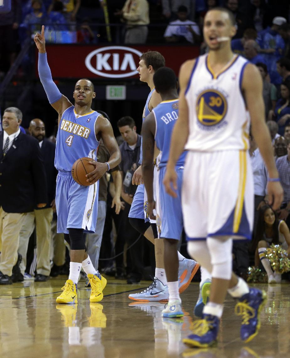 Denver Nuggets' Randy Foye, left, celebrates at the end of an NBA basketball game as Golden State Warriors' Stephen Curry, right, walks off the court Thursday, April 10, 2014, in Oakland, Calif. Denver won, 100-99