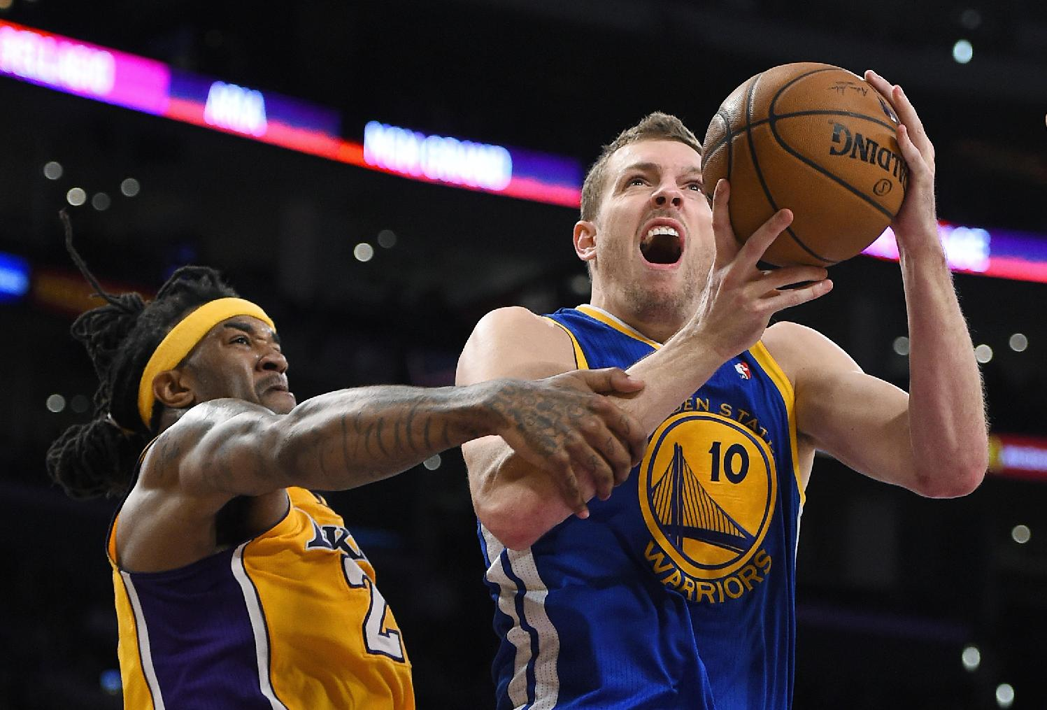 Golden State Warriors forward David Lee shoots as Los Angeles Lakers forward Jordan Hill defends during the second half of an NBA basketball game, Friday, April 11, 2014, in Los Angeles. The Warriors won 112-95