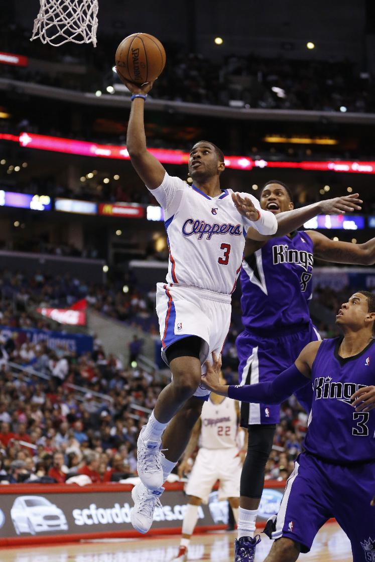 Los Angeles Clippers guard Chris Paul shoots the ball in front of Sacramento Kings forward Rudy Gay, second right, and Kings guard Ray McCallum, right, during the first half of an NBA basketball game in Los Angeles, Sunday, April 12, 2014