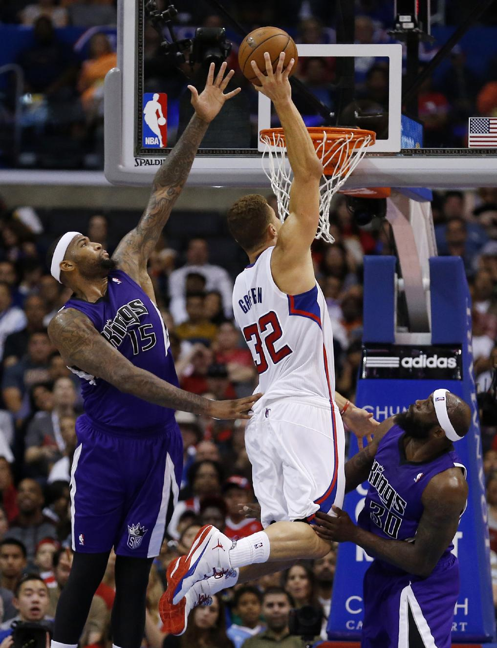Los Angeles Clippers forward Blake Griffin, center, dunks the ball past Sacramento Kings center DeMarcus Cousins, left, and Kings forward Reggie Evans, right, during the second half of an NBA basketball game in Los Angeles, Saturday, April 12, 2014. The Clippers won 117-101