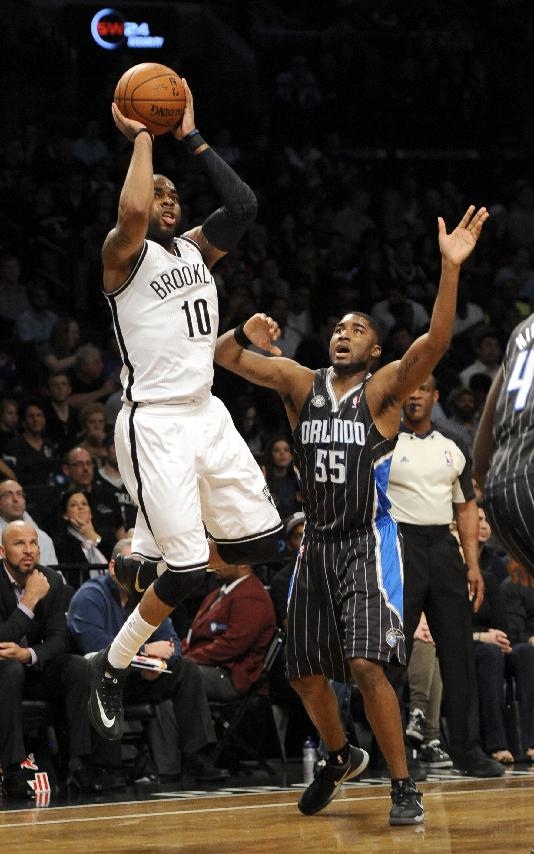 Brooklyn Nets' Marcus Thornton (10) shoots in front of Orlando Magic's E'Twaun Moore (55) during the first half of an NBA basketball game Sunday, April 13, 2014, in New York