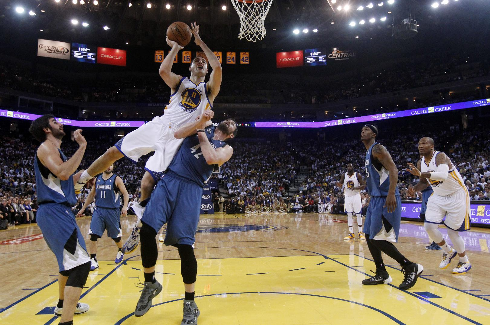 Golden State Warriors' Klay Thompson (11) scores over Minnesota Timberwolves' Kevin Love (42) and Ricky Rubio, left, during the second half of an NBA basketball game on Monday, April 14, 2014, in Oakland, Calif. Golden State won 130-120