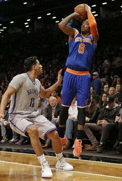 New York Knicks' J.R. Smith (8) shoots over Brooklyn Nets' Jorge Gutierrez (13) during the second half of an NBA basketball game Tuesday, April 15, 2014, in New York. The Knicks won 109-98