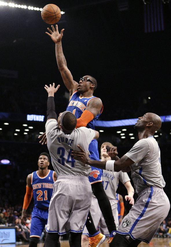 New York Knicks' Amare Stoudemire shoots over Brooklyn Nets' Paul Pierce (34) and Kevin Garnett during the second half of an NBA basketball game Tuesday, April 15, 2014, in New York. The Knics won 109-98