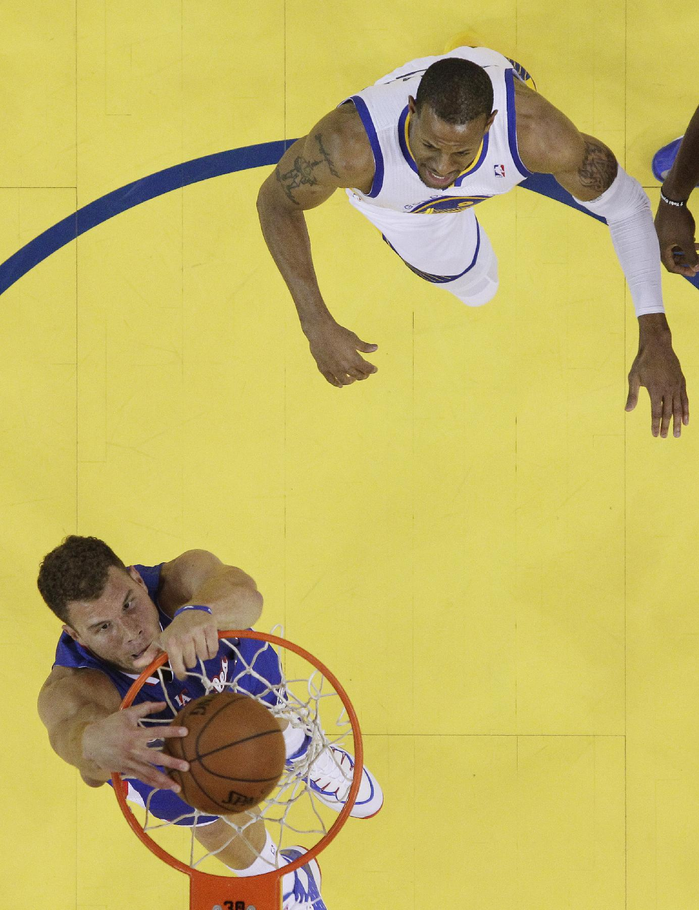 CORRECTS BYLINE - Los Angeles Clippers' Blake Griffin, bottom dunks past Golden State Warriors' Andre Iguodala during the first half in Game 3 of an opening-round NBA basketball playoff series on Thursday, April 24, 2014, in Oakland, Calif. Los Angeles won 98-96