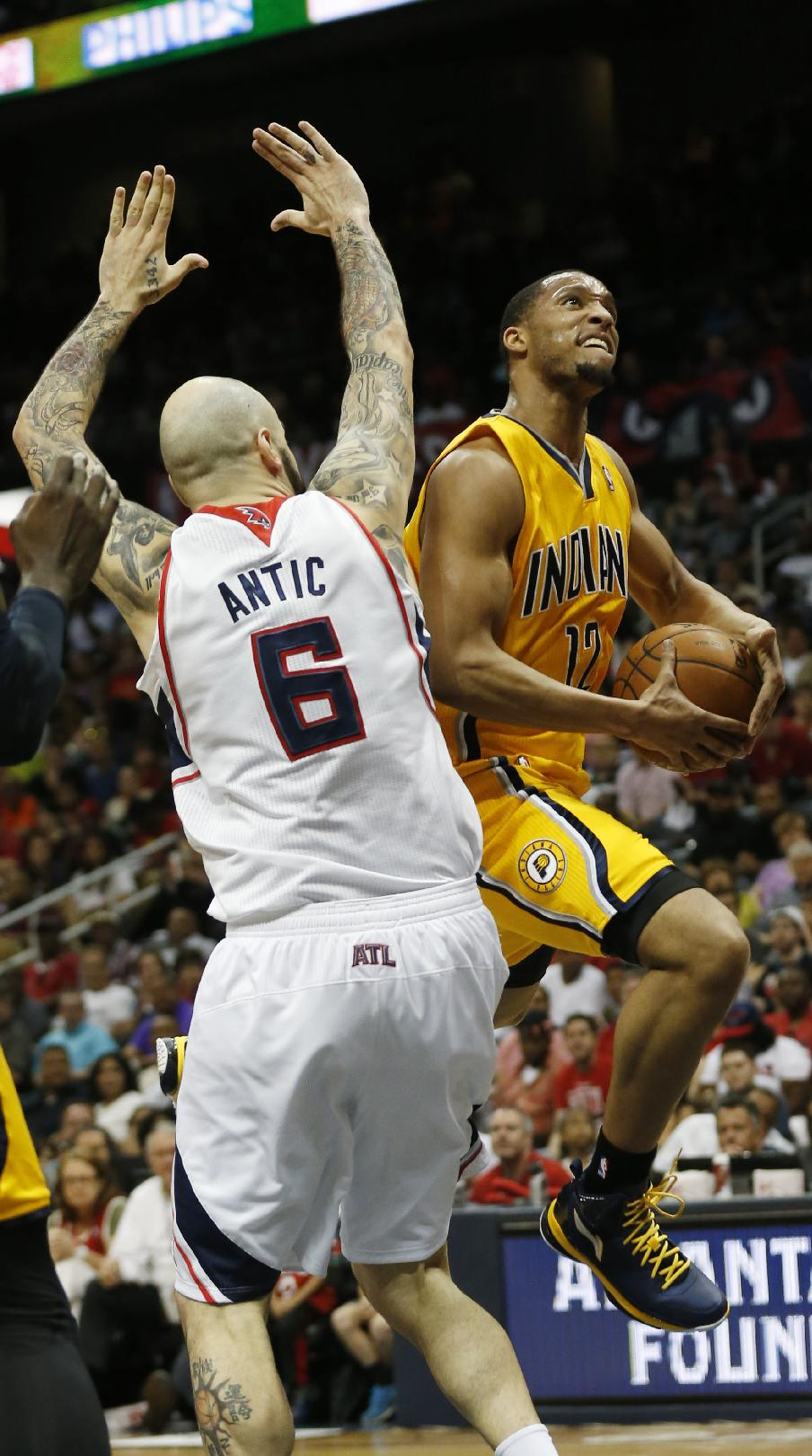 Indiana Pacers forward Evan Turner (12) drives to the basket as Atlanta Hawks center Pero Antic (6) defends in the first half of Game 4 of an NBA basketball first-round playoff series, Saturday, April 26, 2014, in Atlanta