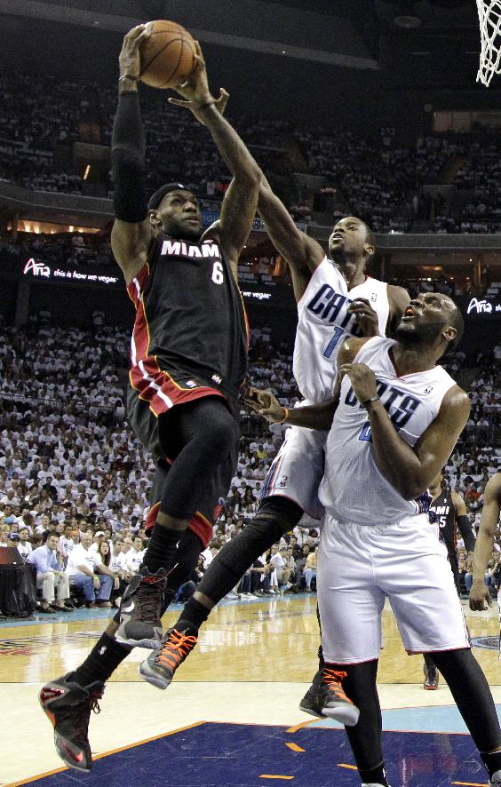 Miami Heat's LeBron James, left, shoots over Charlotte Bobcats' Michael Kidd-Gilchrist, center, and Al Jefferson, right, during the first half in Game 3 of an opening-round NBA basketball playoff series in Charlotte, N.C., Saturday, April 26, 2014