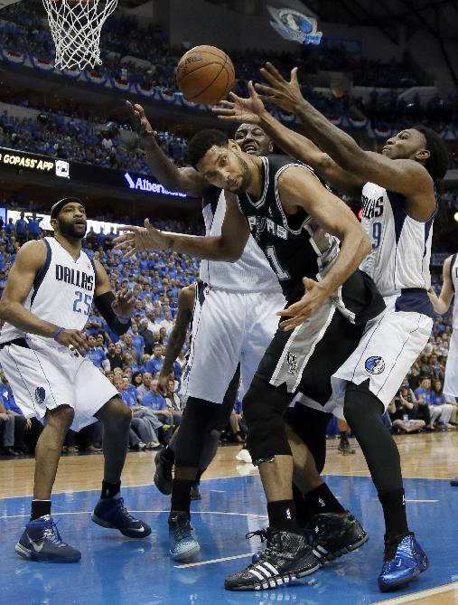 San Antonio Spurs' Tim Duncan, center, loses track of a rebound as Dallas Mavericks' DeJuan Blair, center rear, and Jae Crowder (9) reach over to grab the loose ball in the second half of Game 4 of an NBA basketball first-round playoff series, Monday, April 28, 2014, in Dallas. Mavericks' Vince Carter (25) watches the play in the 93-89 Spurs win