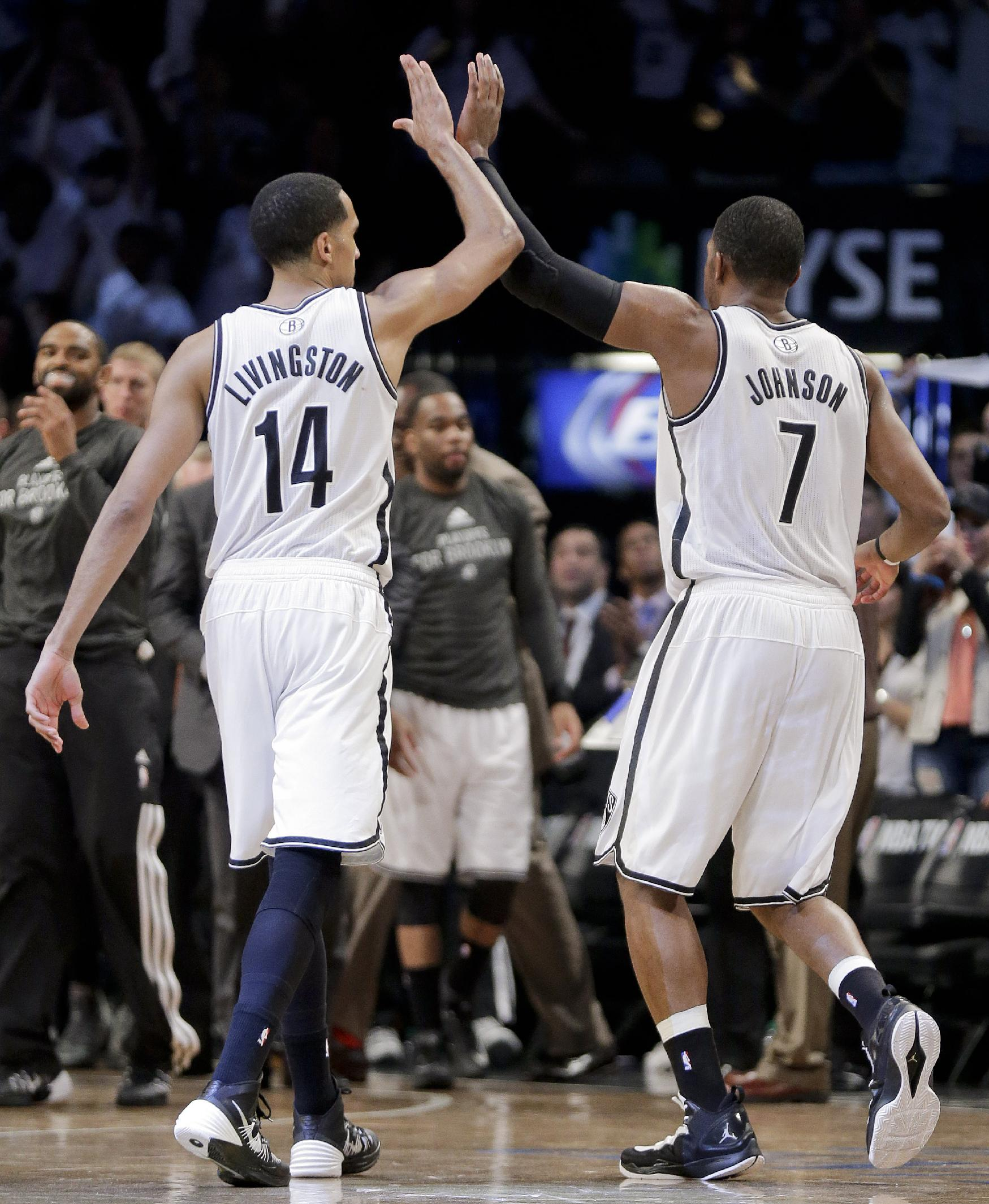Brooklyn Nets guard Shaun Livingston (14) and guard Joe Johnson (7) high-five as they walk to the bench during timeout in the fourth quarter against the Miami Heat during Game 3 of an Eastern Conference semifinal NBA playoff basketball game on Saturday, May 10, 2014, in New York. The Nets won 104-90