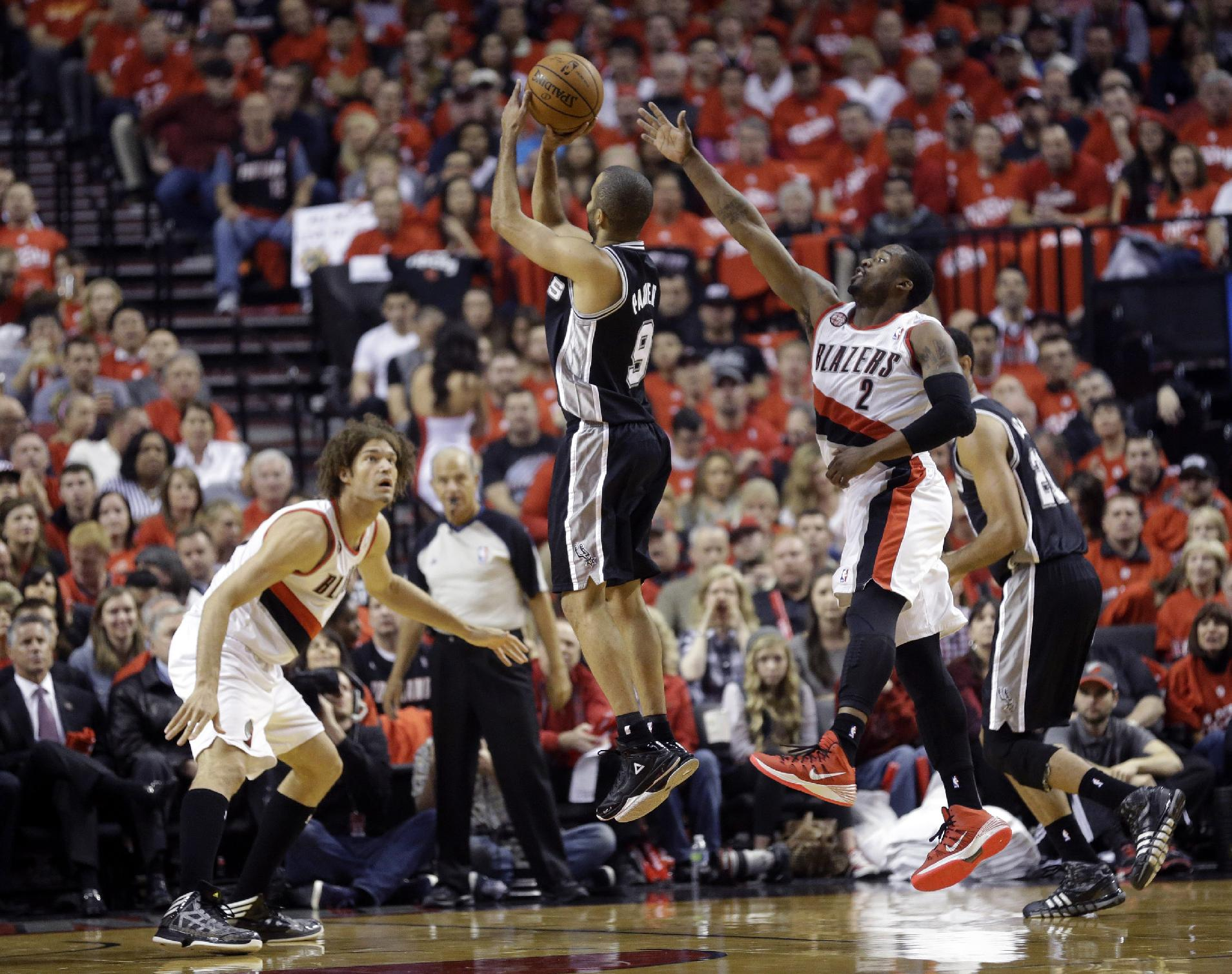 San Antonio Spurs' Tony Parker (9) shoots as Portland Trail Blazers' Robin Lopez (42) and Wesley Matthews (2) defend in the first quarter during Game 3 of a Western Conference semifinal NBA basketball playoff series Saturday, May 10, 2014, in Portland, Ore