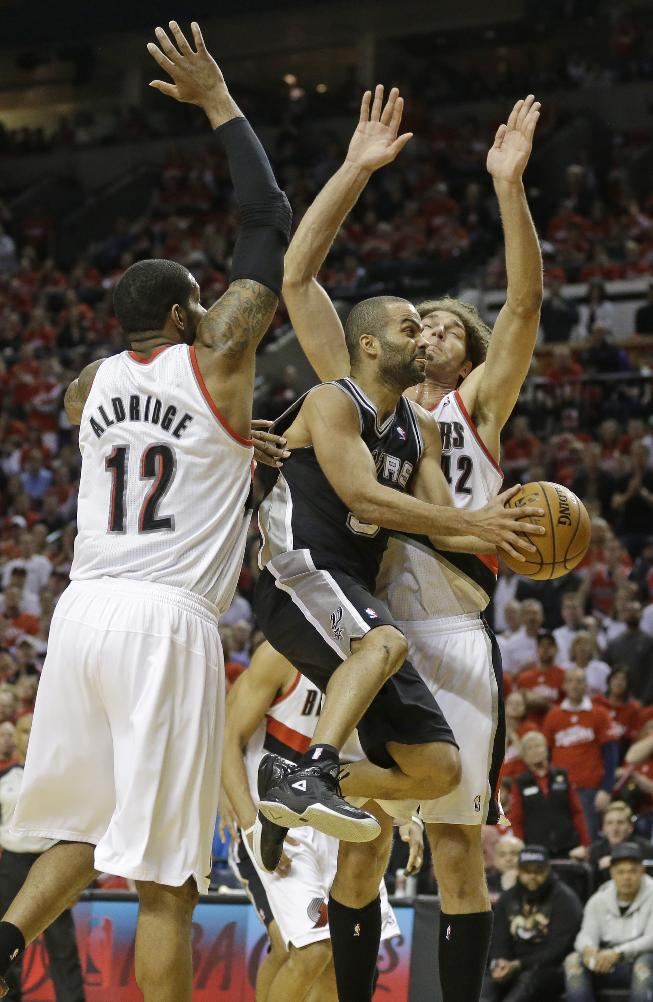 San Antonio Spurs' Tony Parker (9) drives to the basket as Portland Trail Blazers' LaMarcus Aldridge (12) and Robin Lopez, right, defend in the third quarter during Game 3 of a Western Conference semifinal NBA basketball playoff series Saturday, May 10, 2014, in Portland, Ore. The Spurs won 118-103