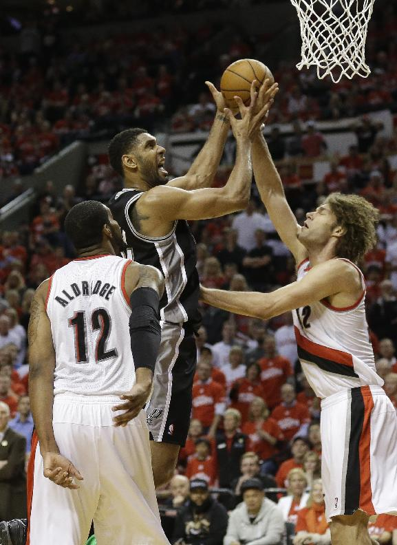 San Antonio Spurs' Tim Duncan, center, shoots as Portland Trail Blazers' Robin Lopez, right, defends while LaMarcus Aldridge (12) looks on in the third quarter during Game 3 of a Western Conference semifinal NBA basketball playoff series Saturday, May 10, 2014, in Portland, Ore. The Spurs won 118-103