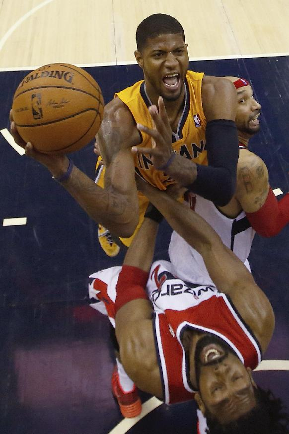 Indiana Pacers forward Paul George, top,  shoots between Washington Wizards forward Nene from Brazil, bottom,and Washington Wizards forward Drew Gooden (90) during the second half of Game 4 of an Eastern Conference semifinal NBA basketball playoff game in Washington, Sunday, May 11, 2014. The Pacers won 95-92