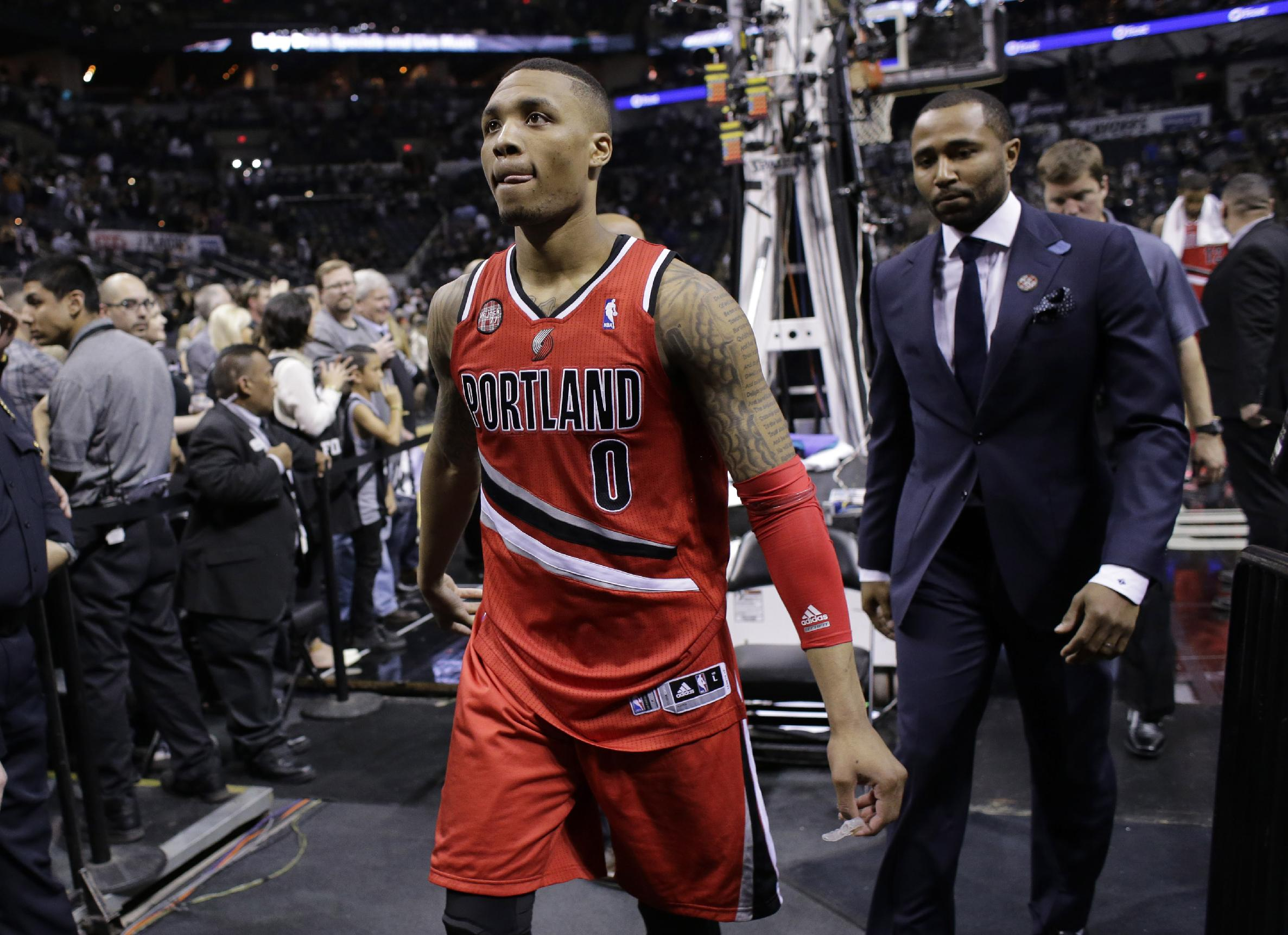 Portland Trail Blazers' Damian Lillard (0) walks off the court following the team's loss in Game 5 of a Western Conference semifinal NBA basketball playoff series, Wednesday, May 14, 2014, in San Antonio. San Antonio won 104-82