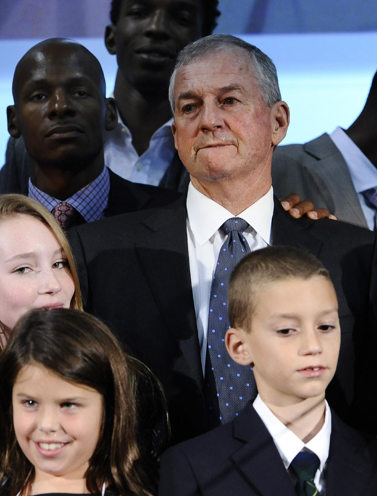 Jim Calhoun, center, stands with his family and former players on stage during a program honoring his coaching career at the University of Connecticut, Sunday, Sept. 22, 2013, in Storrs, Conn. Calhoun retired a year ago with 873 wins and 380 losses after 40 seasons as a head coach, 26 of them at Connecticut