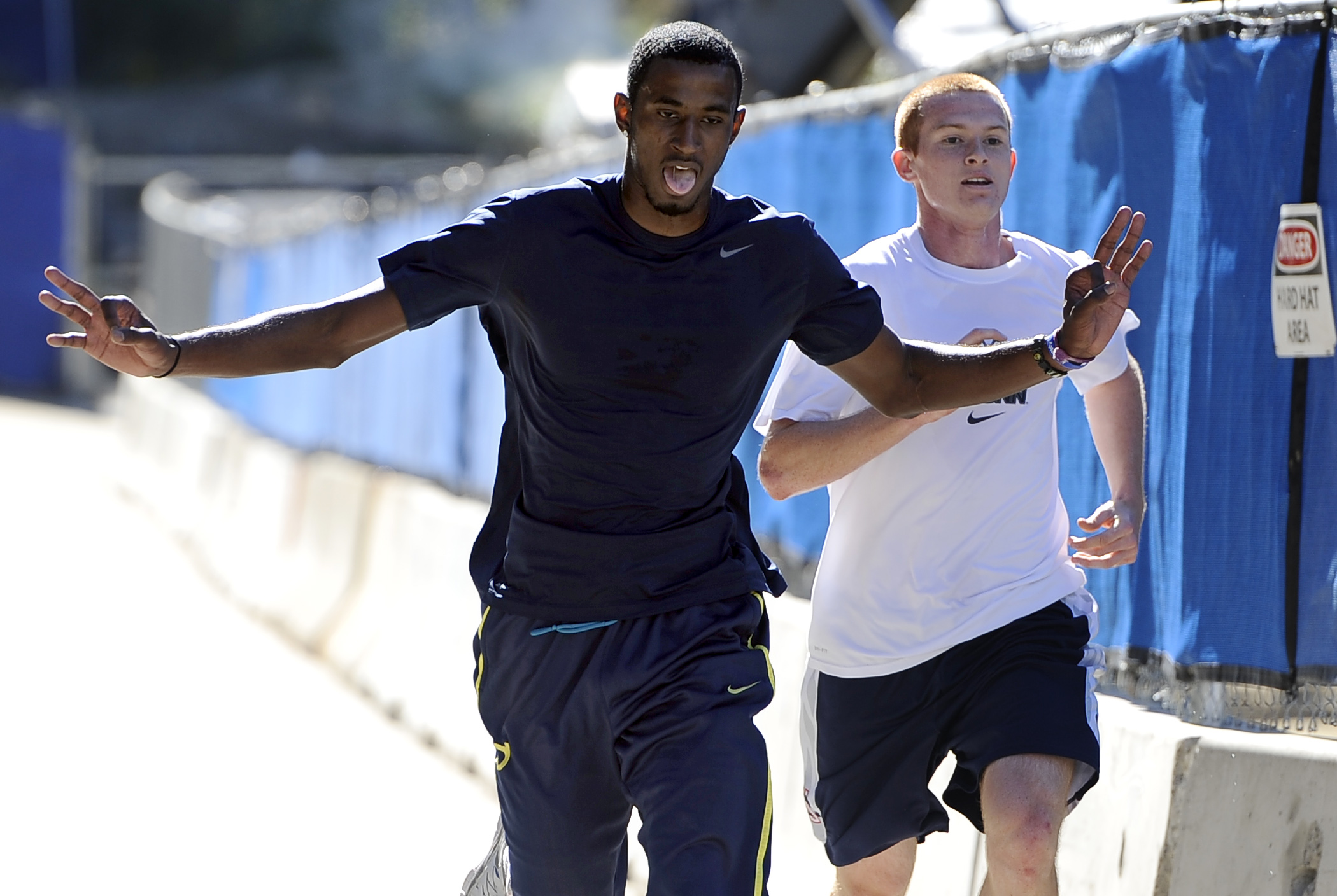 Connecticut basketball player DeAndre Daniels, left, edges out teammate Pat Lenehan to be the first player to finish the 3.4 mile Husky Run, Wednesday, Sept. 25, 2013, in  Storrs, Conn