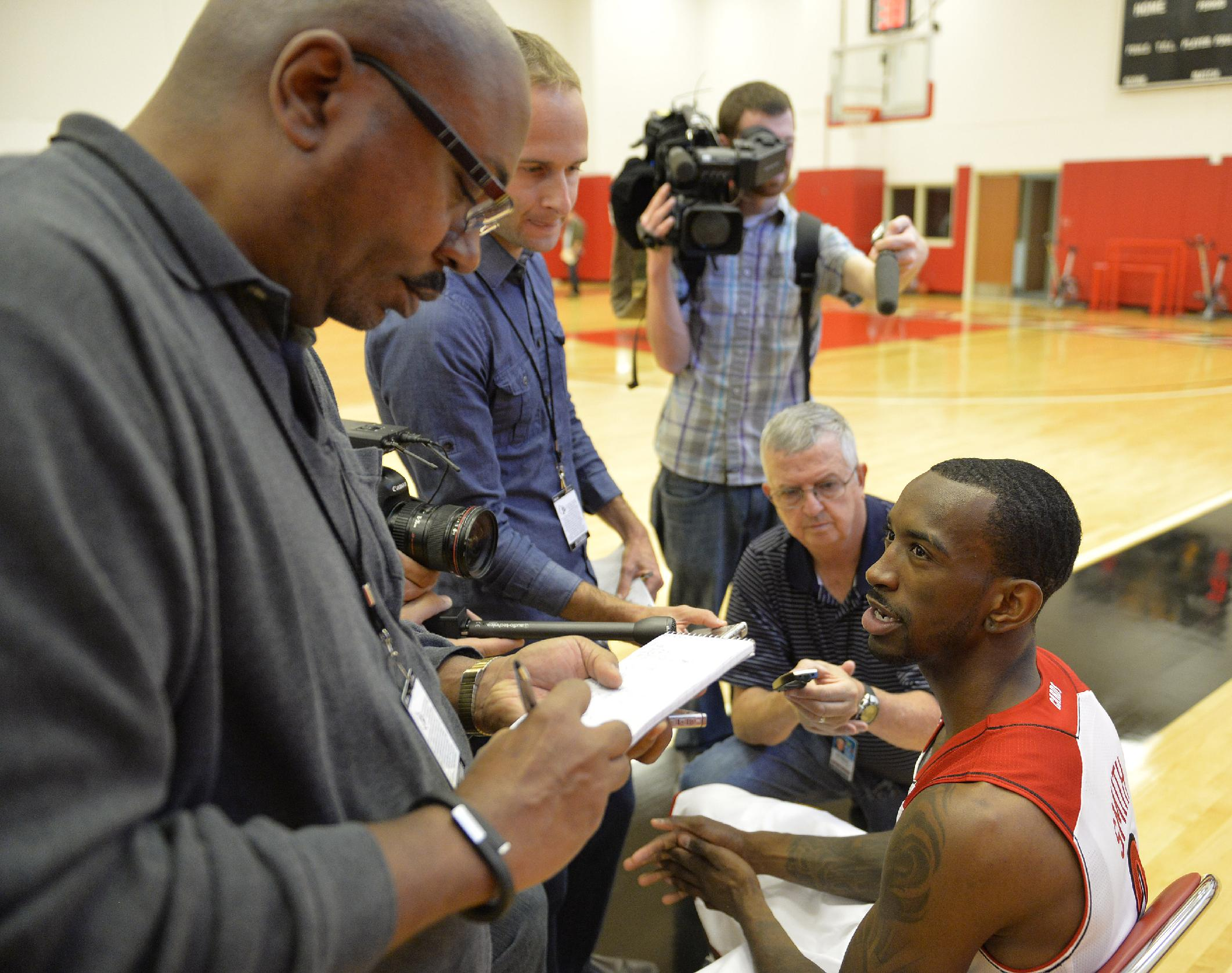 Louisville's Russ Smith, right, answers a reporter's question during NCAA college basketball media day, Saturday, Oct. 12, 2013, in Louisville, Ky