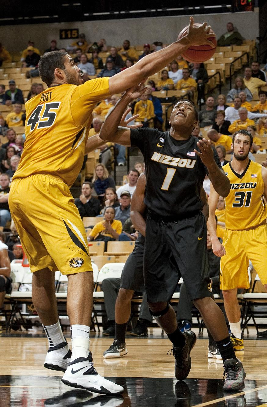 Missouri's Keanau Post, left, pulls down a rebound over Wes Clark, center, as Danny Feldmann, right, watches during an NCAA college basketball scrimmage Tuesday, Oct. 15, 2013, in Columbia, Mo