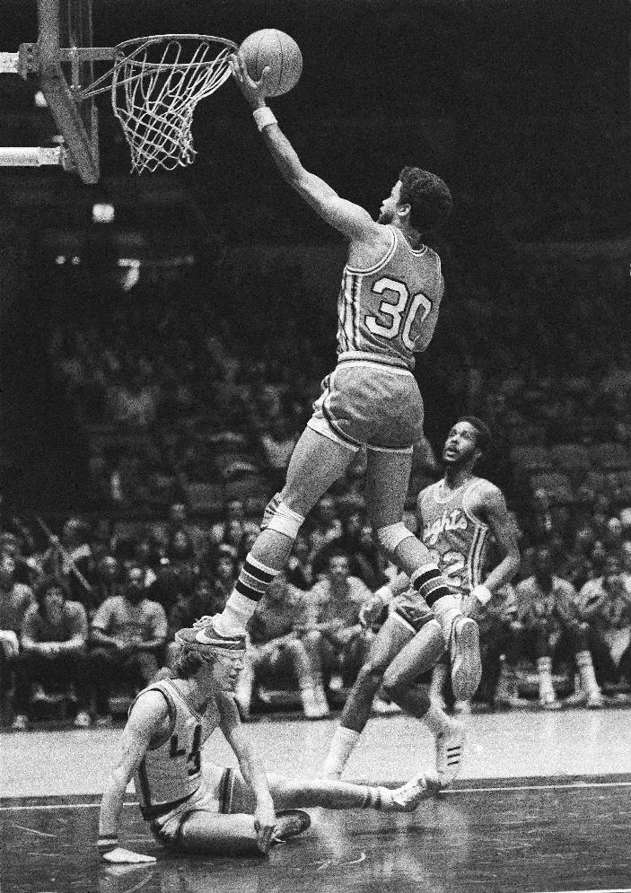 In this Feb. 28, 1976 file photo, Rutgers' Eddie Jordan (30) goes up to score over fallen Bill Rose, of Long Island University, during the first half of an NCAA college basketball game at New York's Madison Square Garden. Rutgers is trying to forget about its recent dark past by reaching into its long-ago storied past. After a turbulent spring in which Mike Rice was fired for berating players and athletic director Tim Pernetti was forced to resign, the Scarlet Knights brought in Eddie Jordan as their 18th head coach