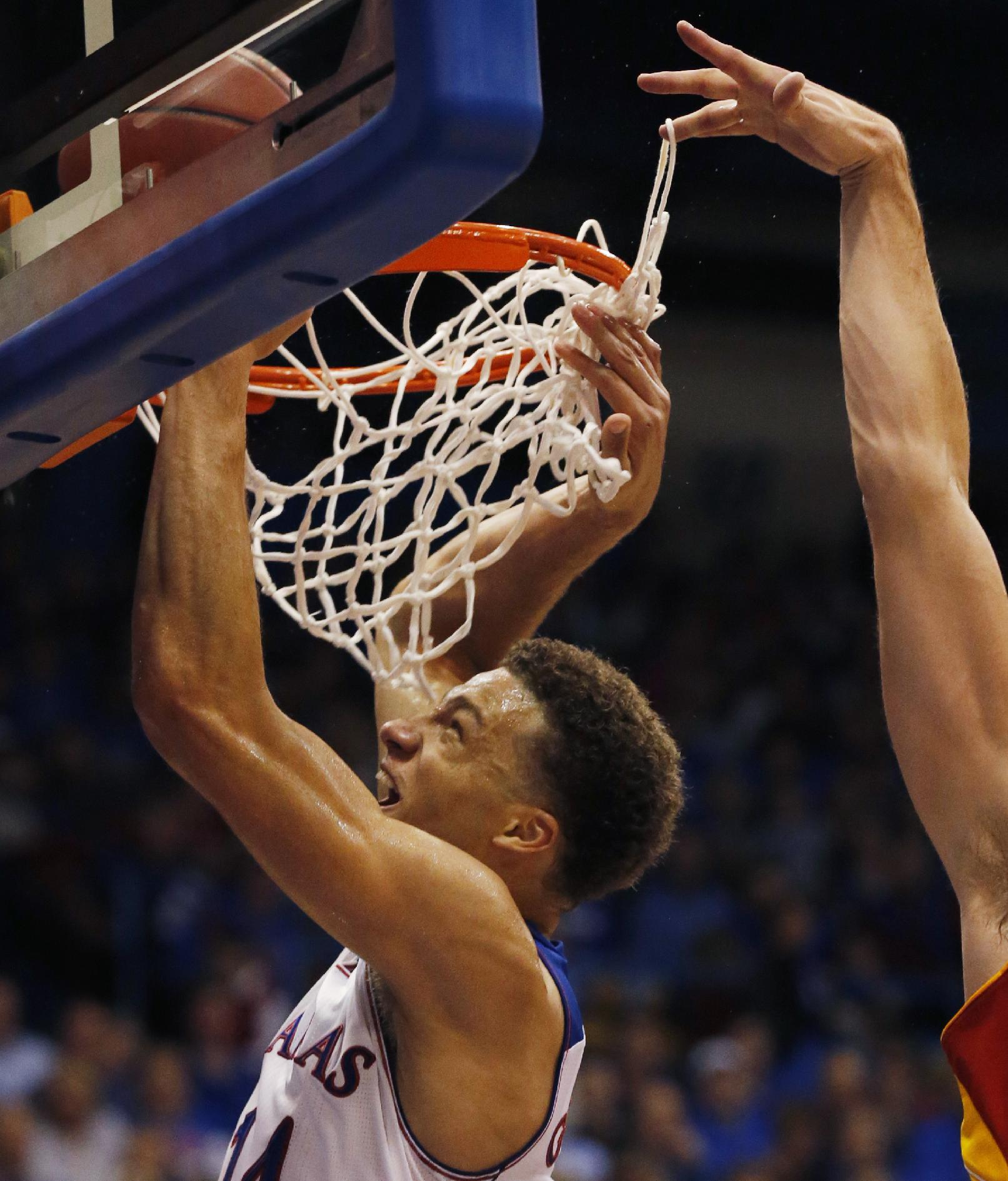 Kansas guard Brannen Greene (14) makes a basket while Pittsburg State forward Cody Gafford, right, gets a finger tangled in the net during the first half of an exhibition NCAA college basketball game in Lawrence, Kan., Tuesday, Oct. 29, 2013. Greene scored 10 points as Kansas won 97-57