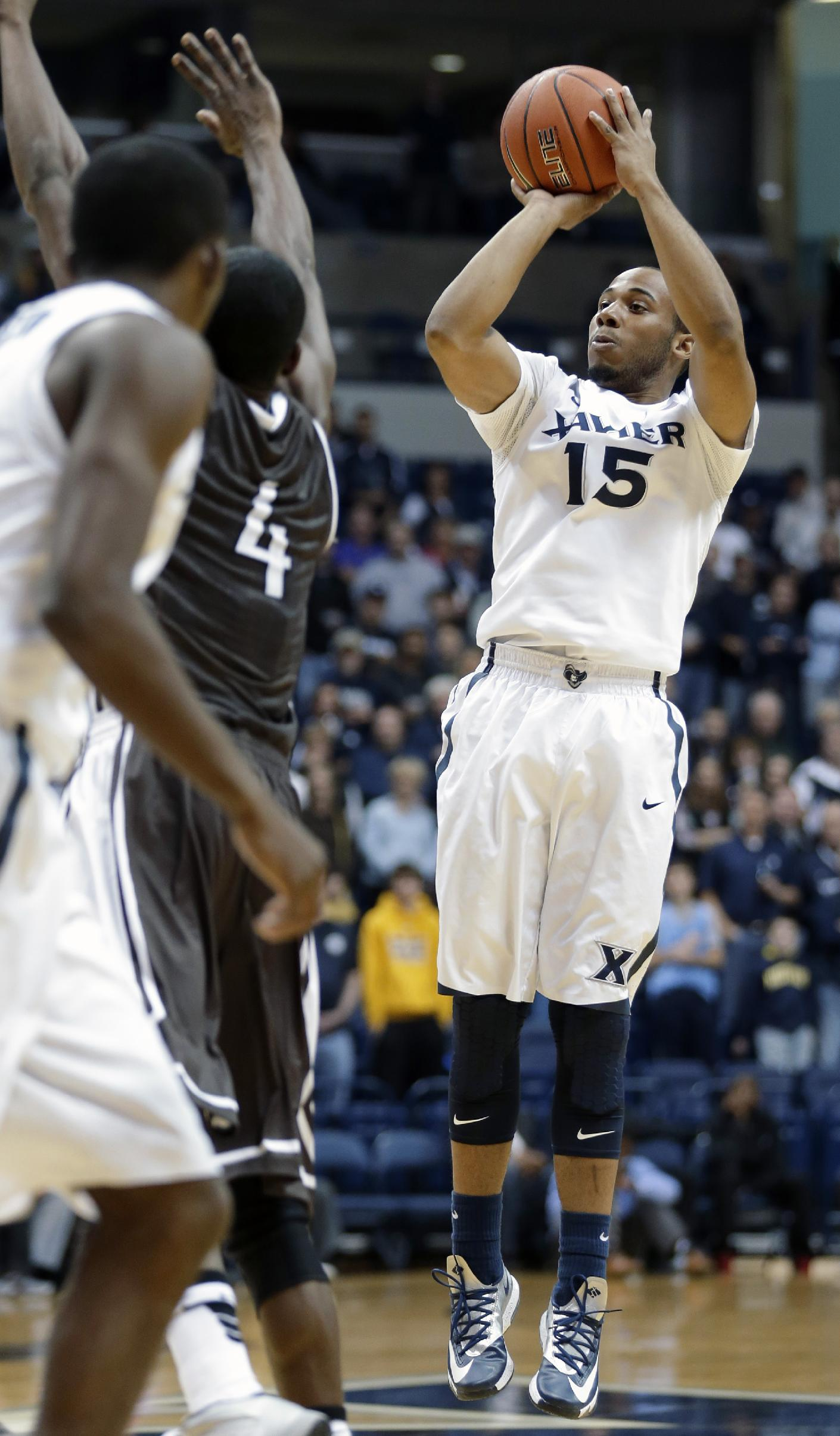 Xavier guard Myles Davis (15) shoots against Quincy in the first half of an NCAA exhibition college basketball game, Saturday, Nov. 2, 2013, in Cincinnati