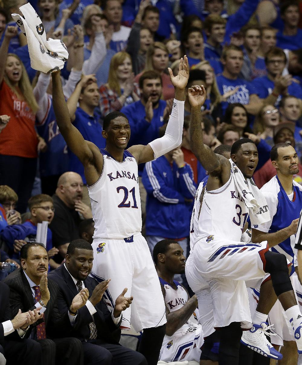 Kansas' Joel Embiid (21) and Jamari Traylor (31) celebrate a teammate's basket during the second half of an exhibition NCAA college basketball game against Fort Hays State University Tuesday, Nov. 5, 2013, in Lawrence, Kan. Kansas won the game 92-75