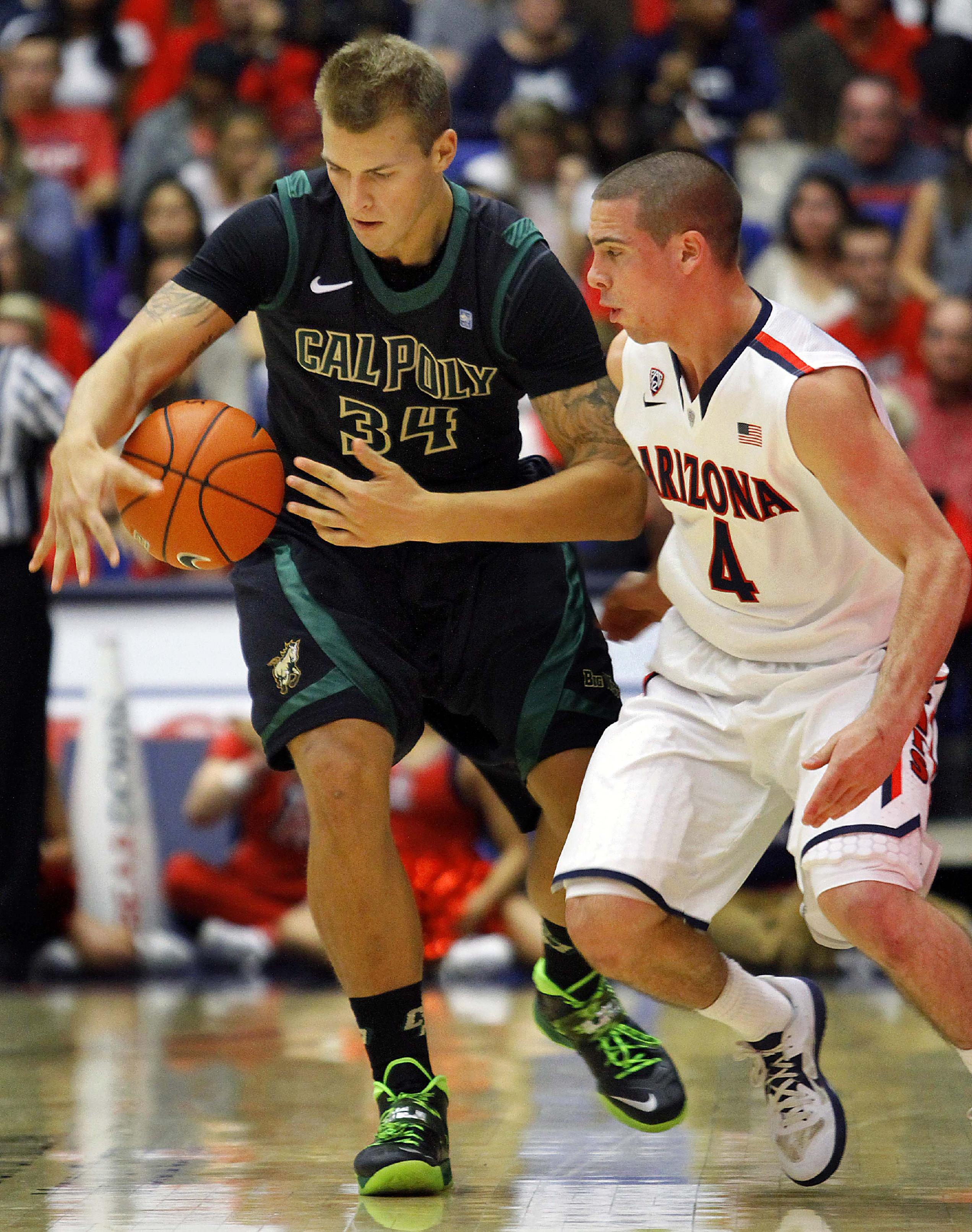 Cal Poy's Brian Benneff (34) and Arizona's T.J. McConnell (4) struggles for a loose ball in the first half of an NCAA college basketball game, Friday, Nov. 8, 2013 in Tucson, Ariz