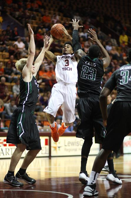 Virginia Tech guard Adam Smith (3) takes a shot under pressure from South Carolina Upstate guard Ty Greene (5), left, and forward Torrey Craig (23), right, during the first half of an NCAA college basketball game in Blacksburg, Va., Saturday, November 9, 2013