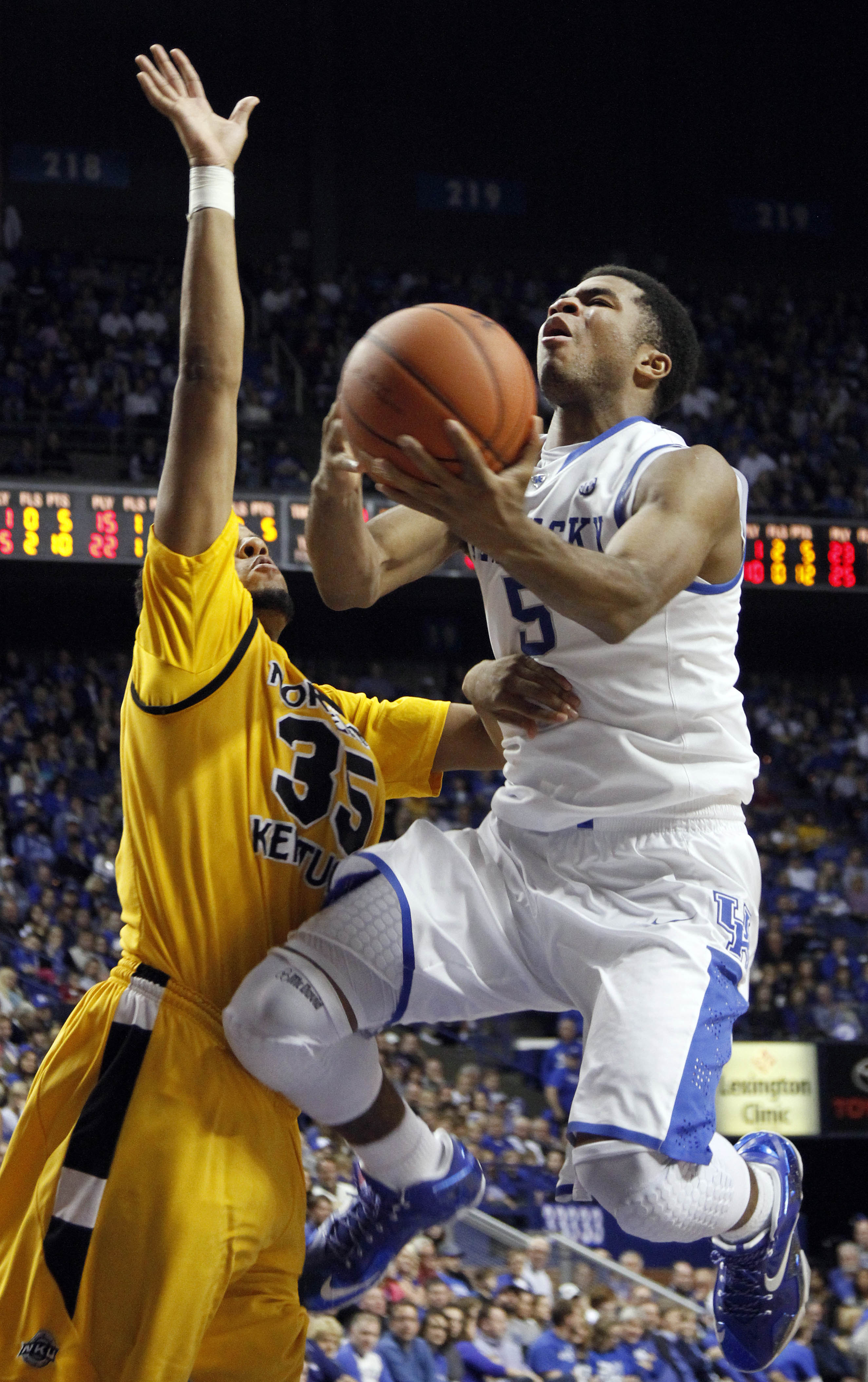 Kentucky's Andrew Harrison (5) shoots under pressure from Northern Kentucky's Deontae Cole (35) during the second half of an NCAA college basketball game, Sunday, Nov. 10, 2013, in Lexington, Ky