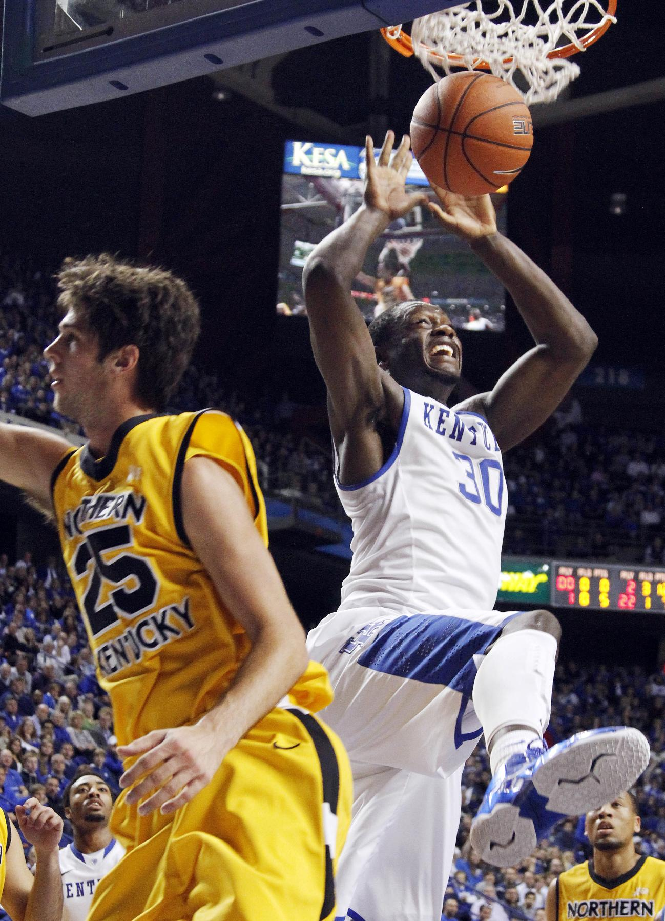 Kentucky's Julius Randle (30) dunks next to Northern Kentucky's Cole Murray (25) during the second half of an NCAA college basketball game Sunday, Nov. 10, 2013, in Lexington, Ky. Kentucky won 93-63