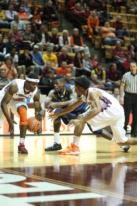 From left, Virginia Tech guard Ben Emelogu (15), West Virginia guard Eron Harris (10), and Virginia Tech guard Adam Smith (3) dive for a loose ball during the first half of an NCAA college basketball game in Blacksburg, Va., Tuesday, Nov. 12, 2013