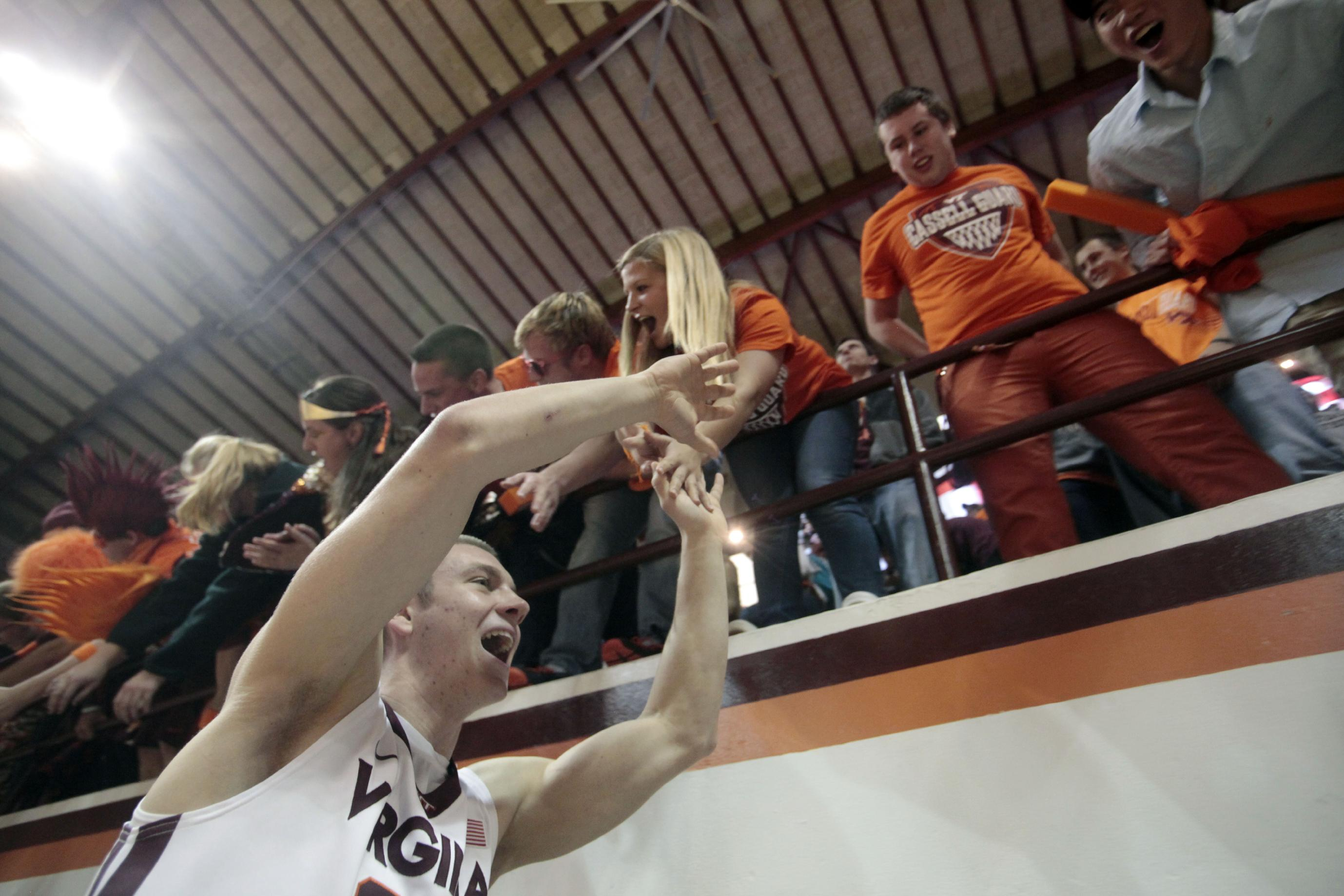 Virginia Tech guard Will Johnston (25) celebrates with fans after defeating West Virginia 87-82 in an NCAA college basketball game in Blacksburg, Va., Tuesday, Nov. 12, 2013