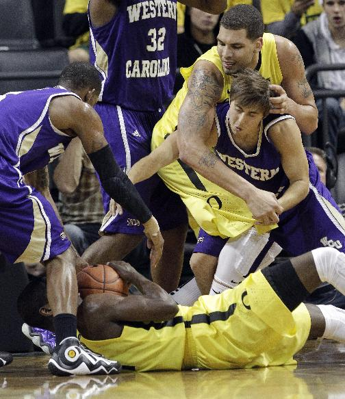 Oregon guard Damyean Dotson holds the ball on the floor as Western Carolina guard Rhett Harrelson, right, grapples with Oregon center Waverly Austin, middle, and Western Carolina guard Trey Sumler moves in at left during the second half of an NCAA college basketball game in Eugene, Ore., Wednesday, Nov. 13, 2013.  Oregon beat Western Carolina 107-83
