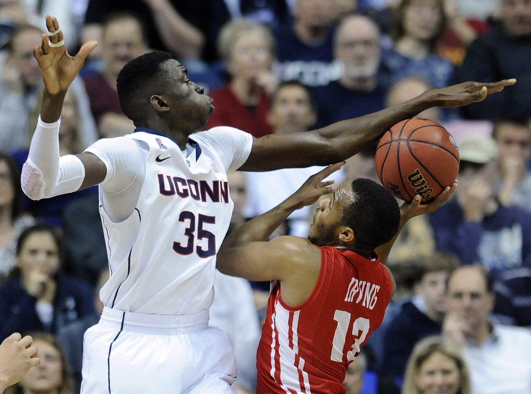 Connecticut's Amida Brimah (35) attempts to block the shot of Boston University's D.J. Irving (13) during the first half of an NCAA college basketball game in Storrs, Conn., on Sunday, Nov. 17, 2013