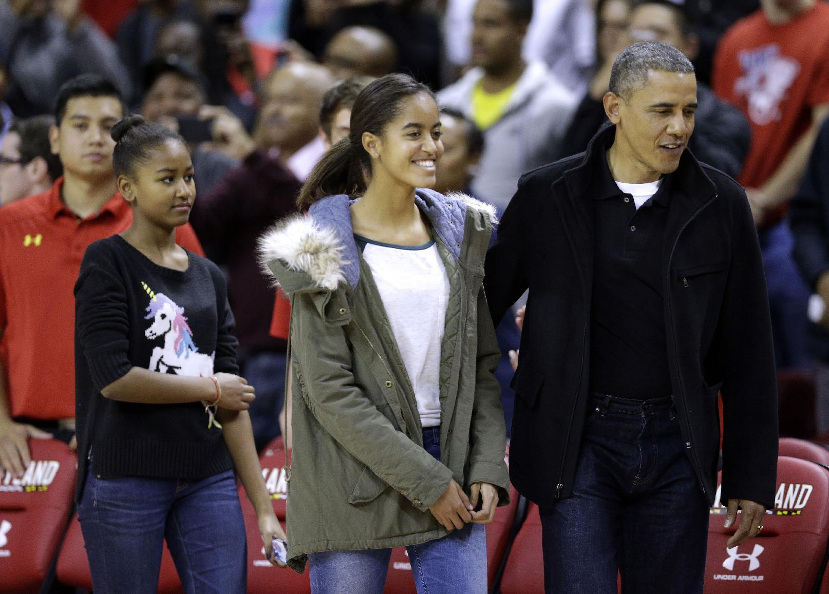 United States President Barack Obama, right, walks to his seat with daughters Sasha, left, and Malia, center, before an NCAA college basketball game between Maryland and Oregon State in College Park, Md., Sunday, Nov. 17, 2013. Obama's brother-in-law is Oregon State head coach Craig Robinson