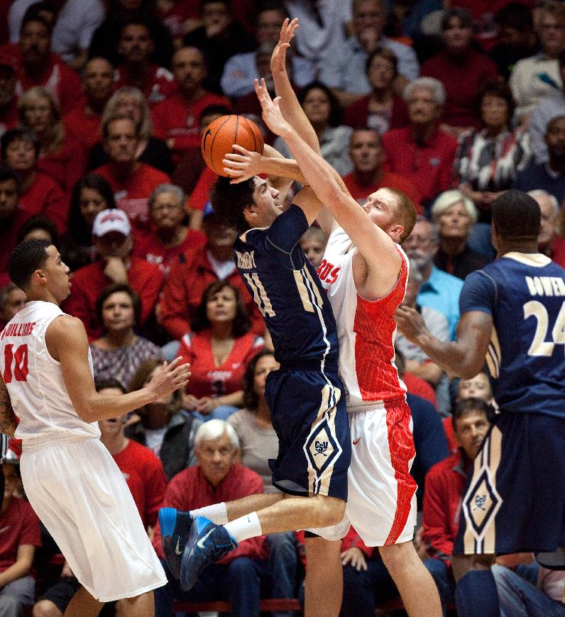 Charleston Southern's Matt Kennedy, second from left, tries to shoot over New Mexico's Alex Kirk in the first half of an NCAA college basketball game Sunday, Nov. 17, 2013, in Albuquerque, N.M.  New Mexico won 109-93