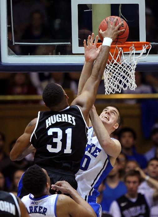 Duke's Marshall Plumlee challenges a shot by UNC-Asheville's Sam Hughes (31) during the first half of an NCAA college basketball game in Durham, N.C., Monday Nov. 18, 2013