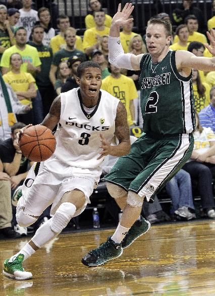 Oregon guard Joseph Young, left, drives to the basket past Utah Valley guard Hayes Garrity during the second half of an NCAA college basketball game in Eugene, Ore., Tuesday, Nov. 19, 2013.  Young led Oregon in scoring with 20 points as they beat Utah Valley 69-54