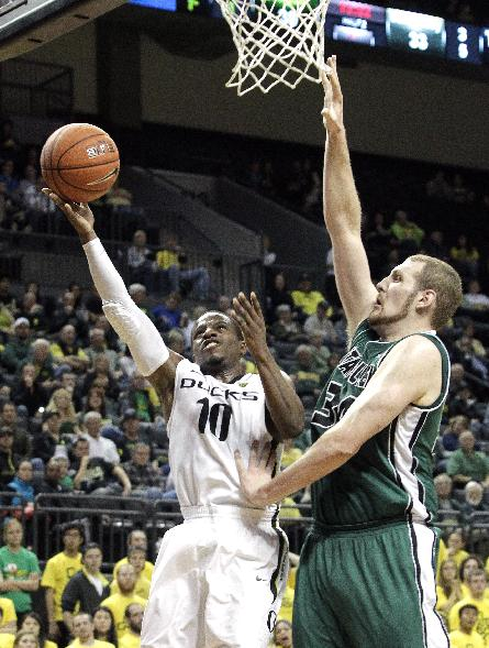 Oregon guard Johnathan Loyd, left, drives to the basket past Utah Valley center Ben Aird  during the second half of an NCAA college basketball game in Eugene, Ore., Tuesday, Nov. 19, 2013.  Loyd scored 12  points as they beat Utah Valley 69-54