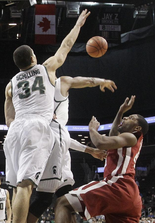 Michigan State's Gavin Schilling (34) blocks a shot by Oklahoma's Cameron Clark (21) during the second half of the championship game in the Coaches vs. Cancer NCAA college basketball game Saturday, Nov. 23, 2013, in New York. Michigan State won 87-76