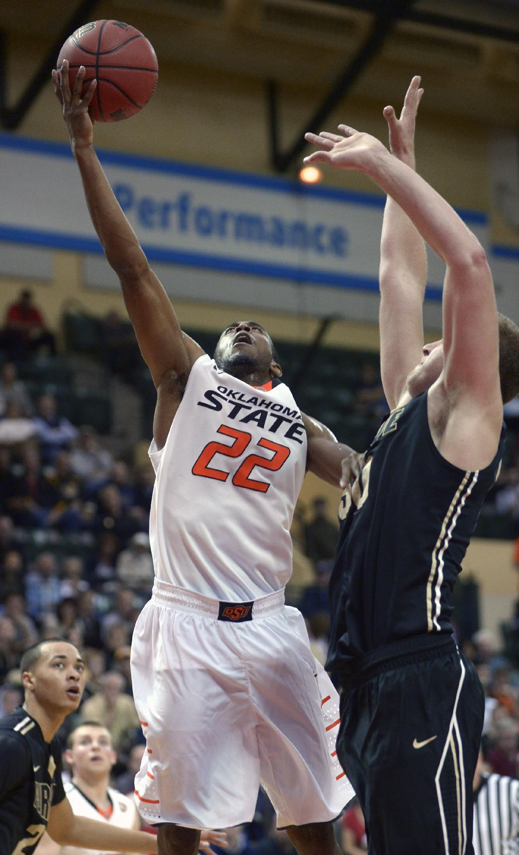 Oklahoma State's Markel Brown (22) puts up a shot in front of Purdue forward Travis Carroll, right, during the second half of an NCAA college basketball game in Kissimmee, Fla., Thursday, Nov. 28, 2013