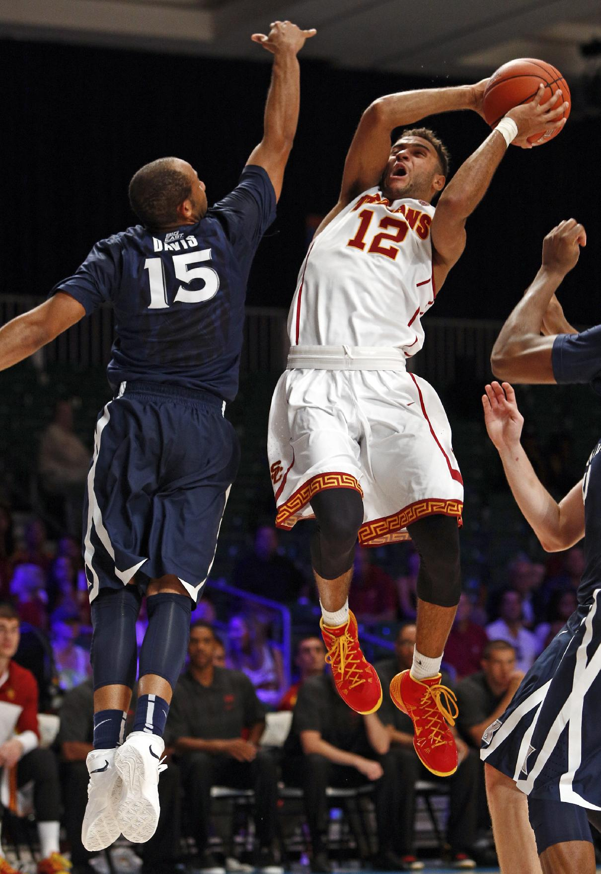 Southern California's Julian Jacobs, right, drives up to the basket avoiding the block of Xavier's Myles Davis during the second half of an NCAA college basketball game in Paradise Island, Bahamas, Saturday, Nov. 30, 2013. USC won 84-78