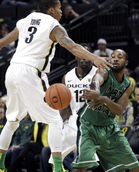 North Dakota guard Jamal Webb, right, passes off as Oregon's Joseph Young, left, and Jason Calliste double-team him at midcourt during the first half of an NCAA college basketball game in Eugene, Ore., Saturday, Nov. 30, 2013