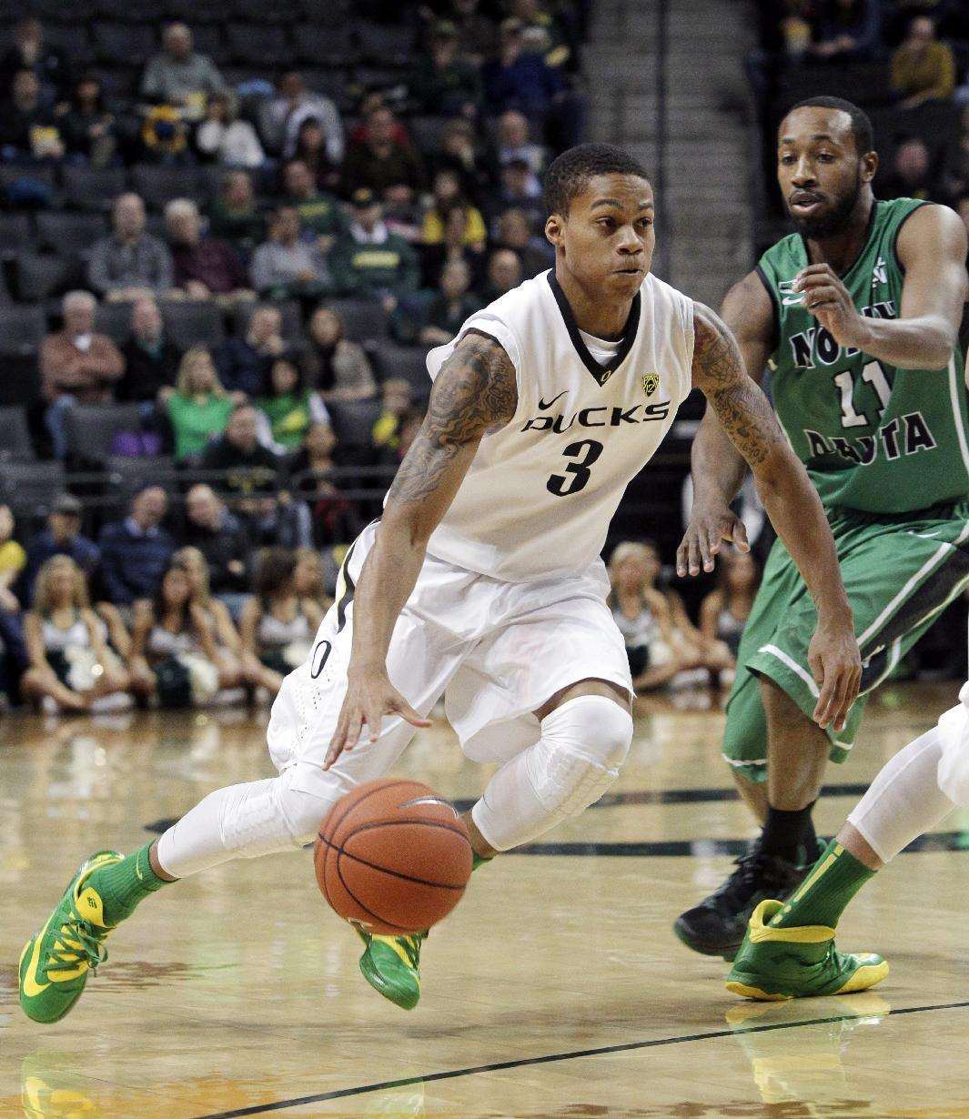 Oregon guard Joseph Young, left, drives past North Dakota guard Jamal Webb during the first half of an NCAA college basketball game in Eugene, Ore., Saturday, Nov. 30, 2013