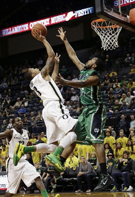 Oregon guard Joseph Young, top left, drives to the basket against North Dakota guard Jamal Webb during the first half of an NCAA college basketball game in Eugene, Ore., Saturday, Nov. 30, 2013