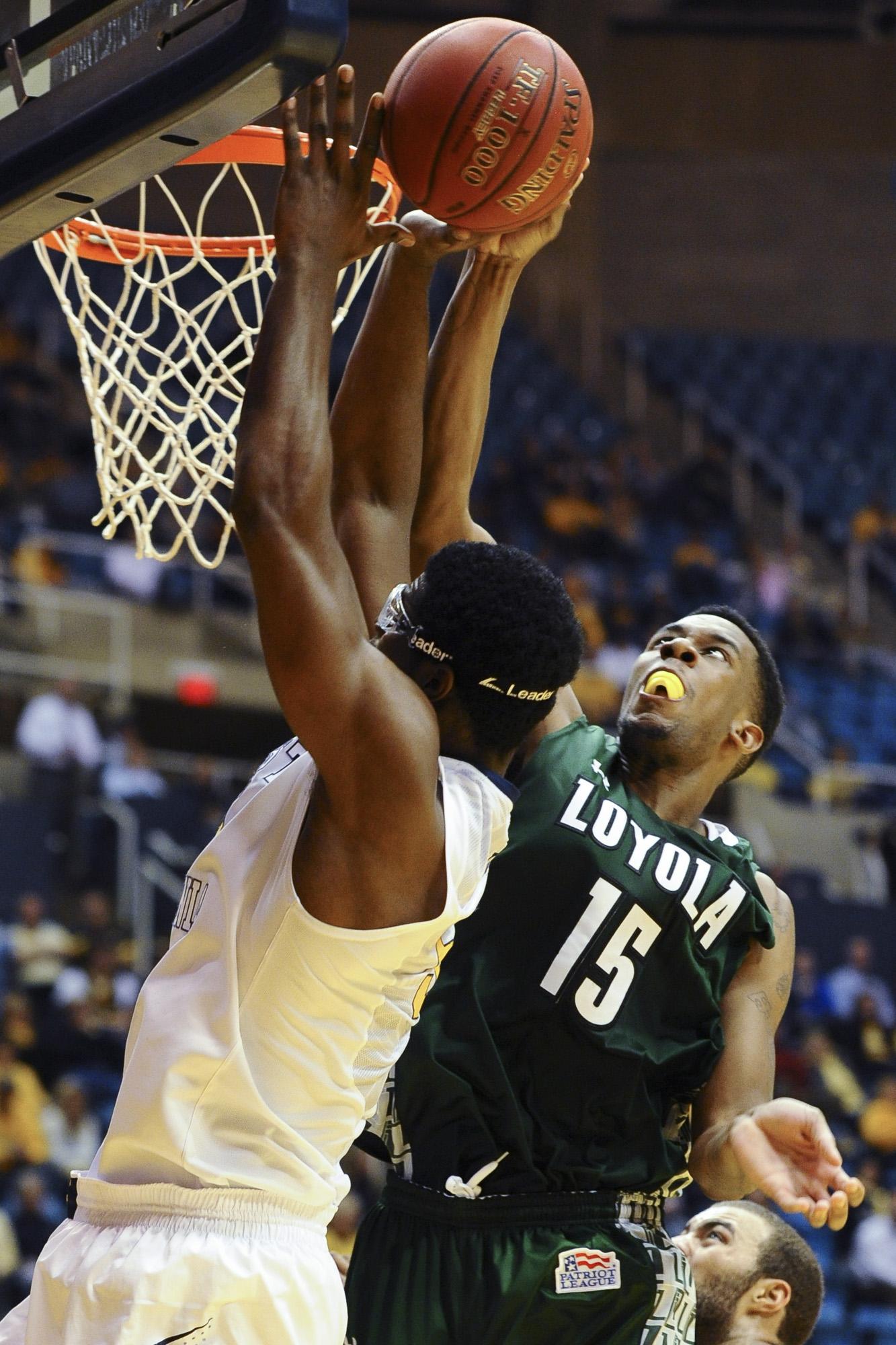 Loyola Maryland's Jordan Latham (15) blocks West Virginia's Devin Williams (left) during the second half of an NCAA college basketball game Monday, Dec. 2, 2013, in Morgantown, W.Va. West Virginia won 96-47